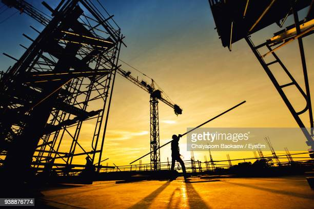 Silhouette Man Working At Construction Site Against Sky During Sunset