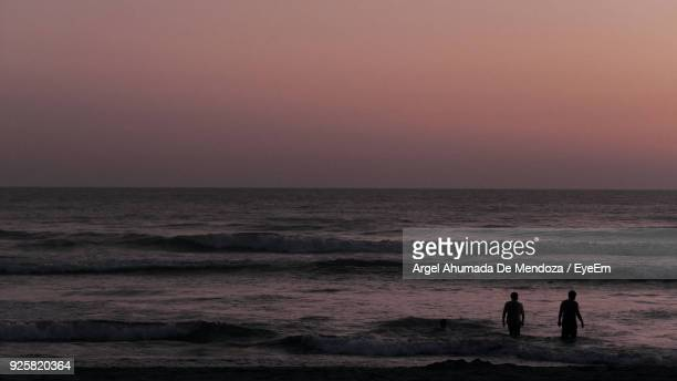 Silhouette Men At Beach Against Sky During Sunset