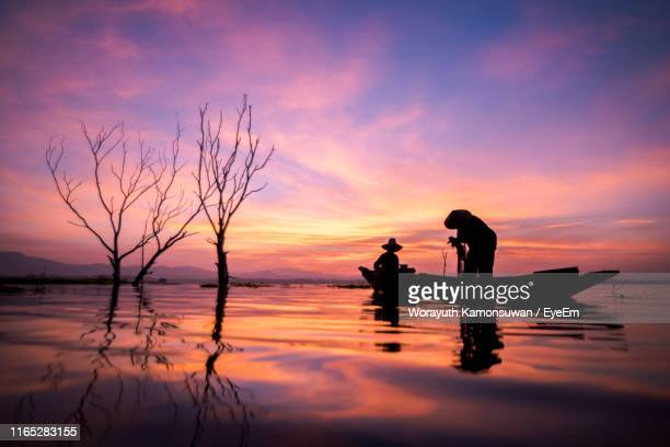 silhouette men fishing in lake against sky during sunset - chonburi province stock pictures, royalty-free photos & images