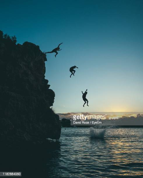 silhouette men jumping from cliff into sea during sunset - david cliff stock pictures, royalty-free photos & images