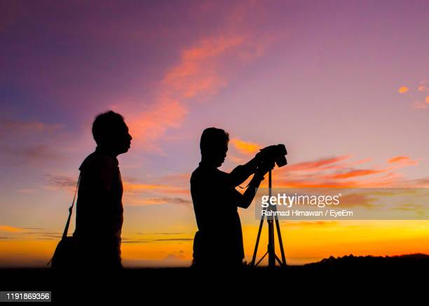 silhouette men photographing against sky during sunset - rahmad himawan stock photos and pictures