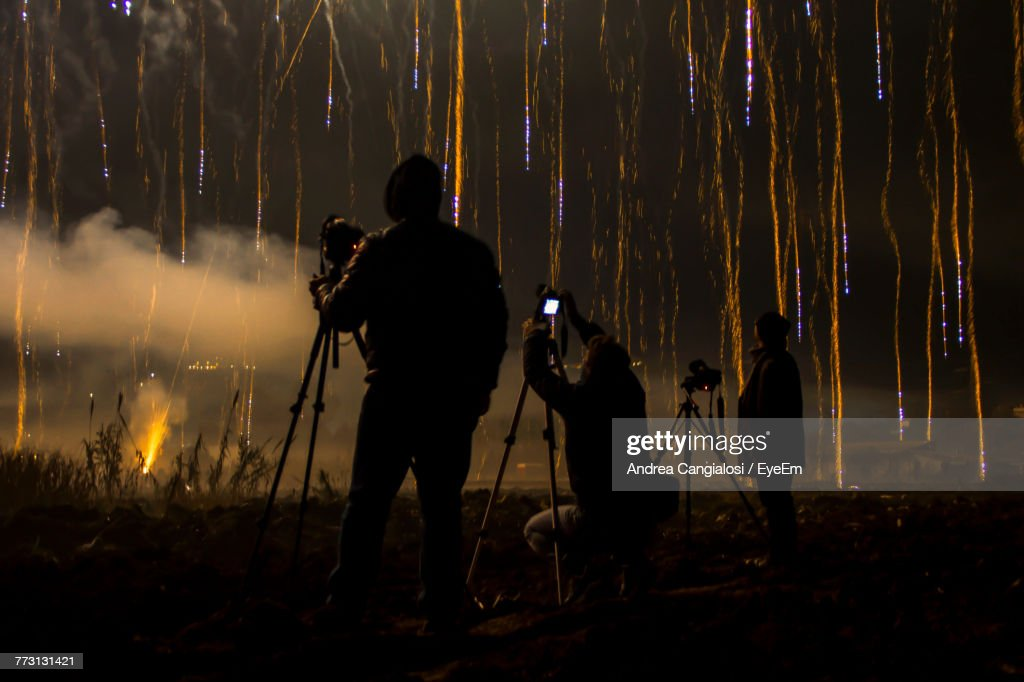 Silhouette Men Photographing Firework Display At Night : Stock Photo