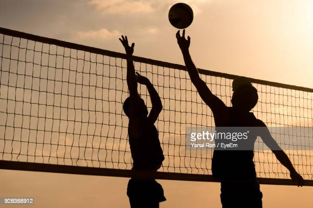 silhouette men playing volleyball against sky during sunset - beachvolleybal stockfoto's en -beelden