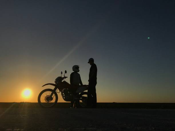 Silhouette Men Sitting On Bicycle Against Sky During Sunset