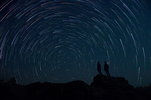 Silhouette Men Standing On Rocks Against Star Trail At Night - gettyimageskorea