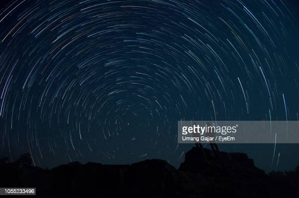 silhouette men standing on rocks against star trail at night - star trail stock pictures, royalty-free photos & images
