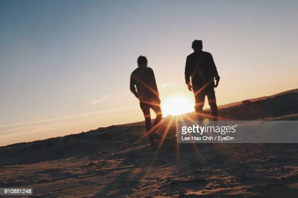 Silhouette Men Walking On Landscape Against Sky During Sunset