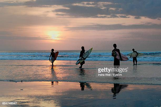 Silhouette Men With Surfboards Standing At Beach During Sunset