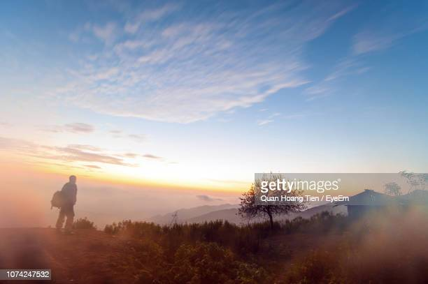 silhouette mid adult man standing on mountain against sky during sunset - son la stock pictures, royalty-free photos & images
