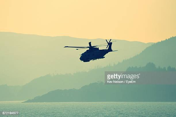 silhouette military helicopter flying over lake against mountains - military stock pictures, royalty-free photos & images