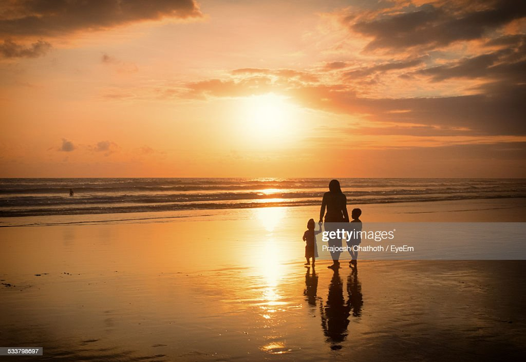 Silhouette Mother And Children Walking On Beach During Sunset : Foto stock