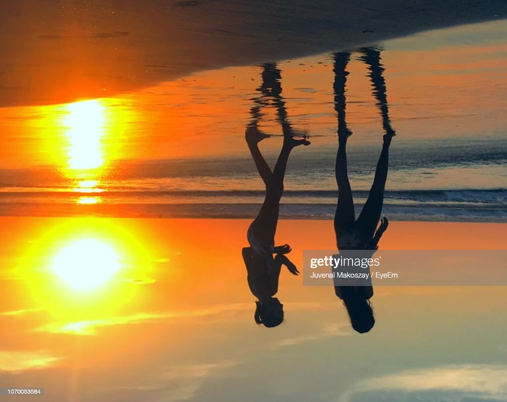 Silhouette Mother And Daughter Walking At Beach Against Orange Sky : Stock Photo
