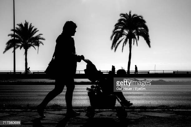 Silhouette Mother Pushing Carriage With Baby Boy