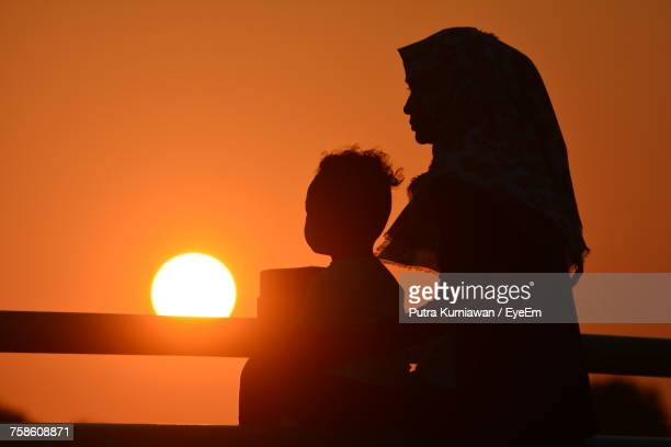 Silhouette Mother With Child Looking At View Against Sky During Sunset