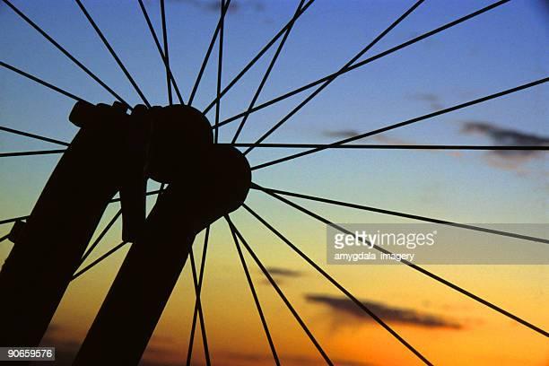 silhouette mountain bike wheel sunset sky - sandia mountains stock photos and pictures