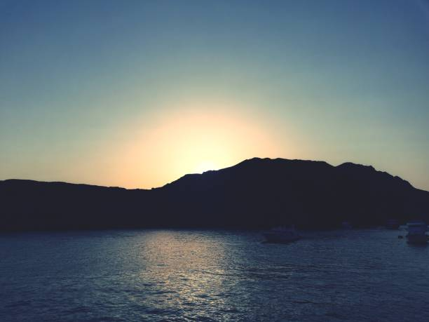 Silhouette Mountain By Sea Against Clear Sky During Sunset