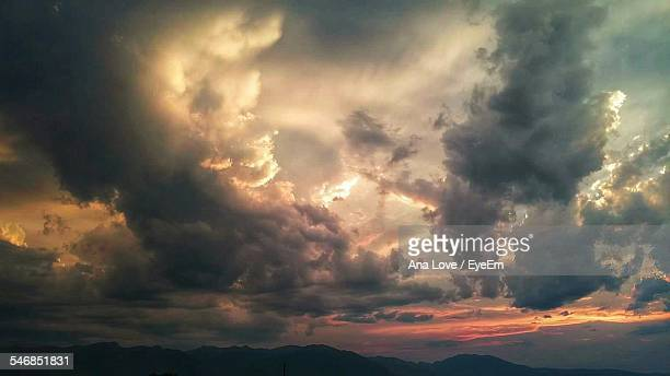 silhouette mountains against cloudy sky during sunset - nuvoloso foto e immagini stock