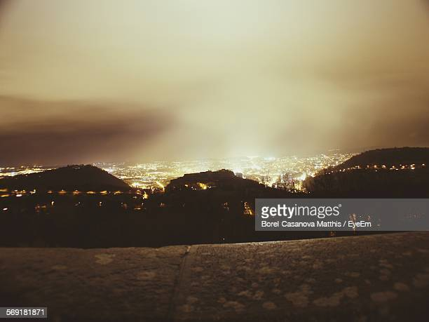 Silhouette Mountains And City Against Cloudy Sky At Night