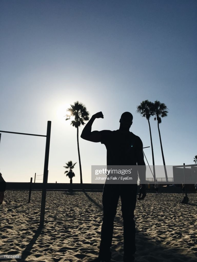 Silhouette Muscular Man Standing On Sand At Beach : Photo