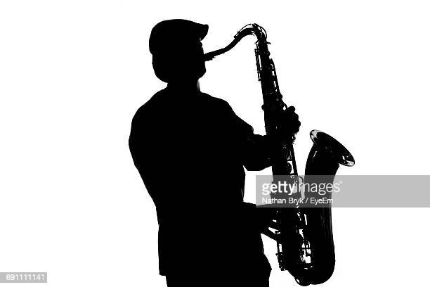 Silhouette Musician Playing Saxophone Against White Background