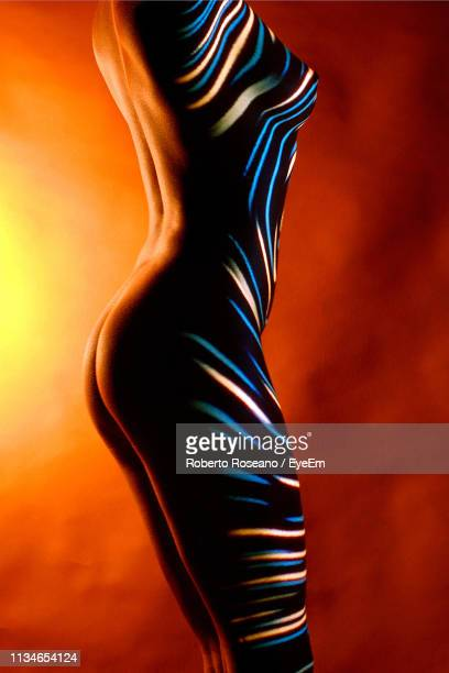silhouette naked woman standing against colored background - beautiful bare bottoms stock pictures, royalty-free photos & images