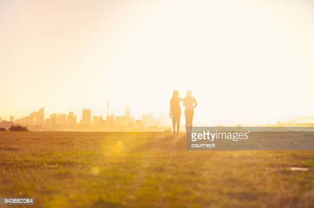 silhouette of 2 women walking in the park. - wide angle stock pictures, royalty-free photos & images