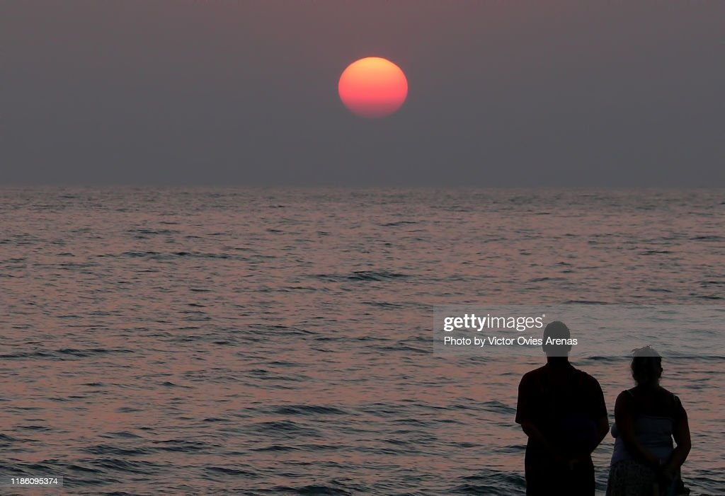 Silhouette of a backlit couple observing the sun setting on the Indian ocean, Goa, India : ストックフォト