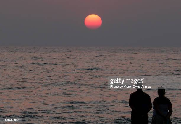 silhouette of a backlit couple observing the sun setting on the indian ocean, goa, india - victor ovies fotografías e imágenes de stock