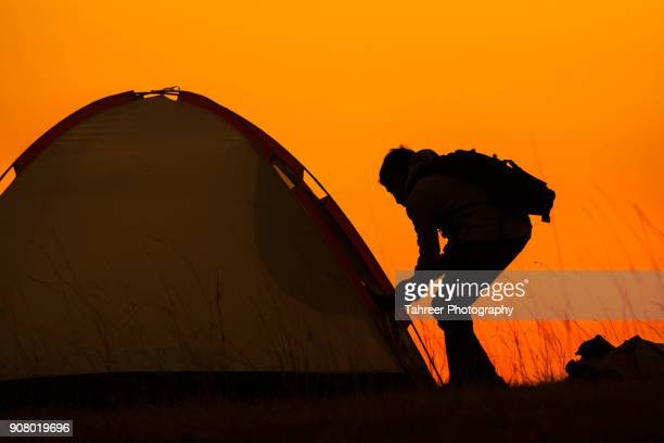 Silhouette of a backpacker opening the camp