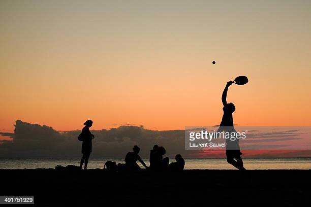 Silhouette of a beach tennis player at sunset
