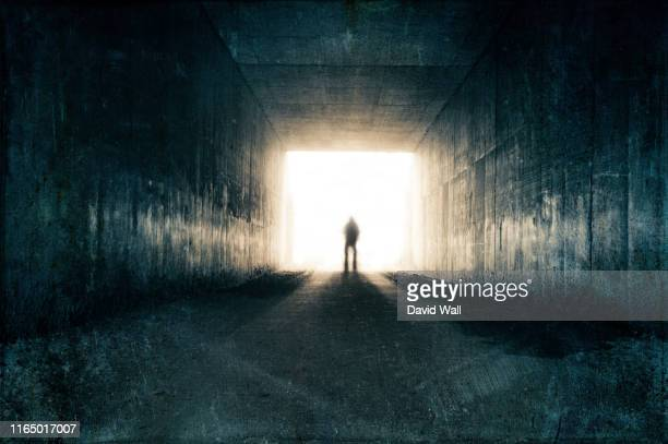 a silhouette of a blurred figure emerging from the light at the end of a dark sinister tunnel. with a grunge, vintage, grainy edit. - tunnel stock pictures, royalty-free photos & images