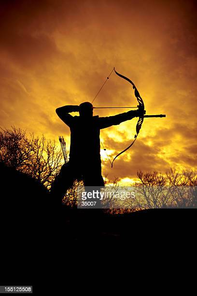 Silhouette of a bow hunter ready to shoot at sunset