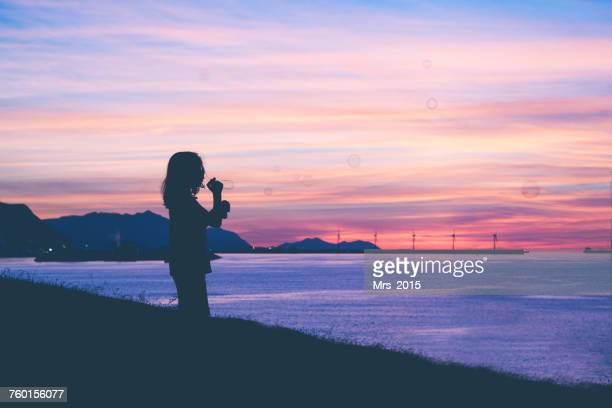Silhouette of a boy blowing soap bubbles at sunset