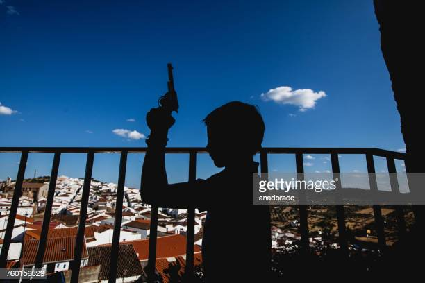 Silhouette of a boy holding a toy gun