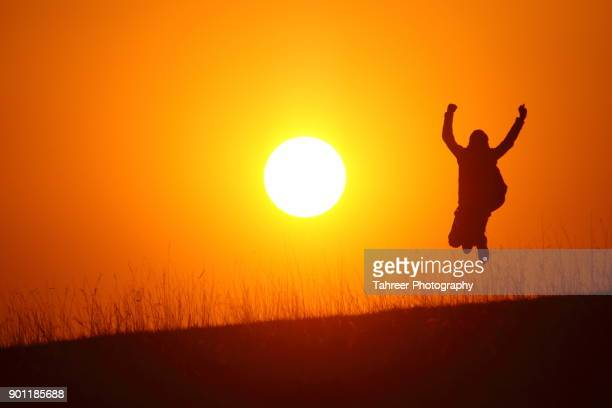 Silhouette of a boy jumping while sun is setting in the background