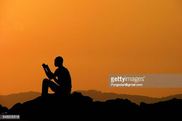 Silhouette of a boy reading a book