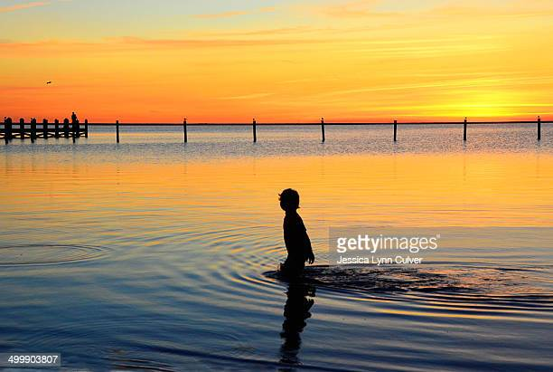 silhouette of a boy walking through water at sunse - lynn pleasant photos et images de collection