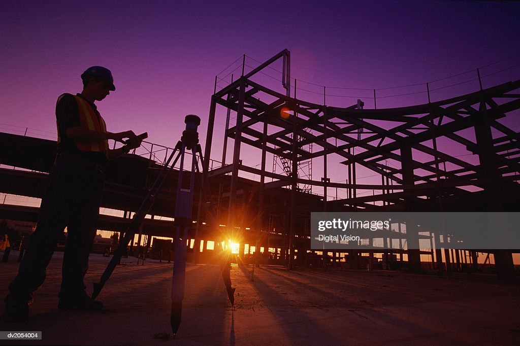 Silhouette of a Builder Working on a Building Site : Stock Photo