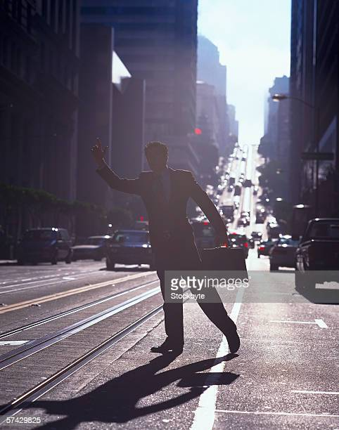 Silhouette of a businessman flagging down a taxi