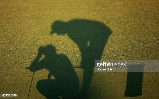 A silhouette of a caddie and player on the 18th green during the second round of the DP World Tour Championship at Jumeirah Golf Estates on November...