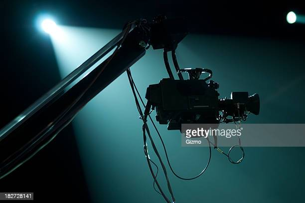 A silhouette of a camera crane in a spotlight