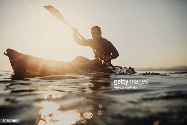 silhouette of a canoeist - wassersport stock-fotos und bilder