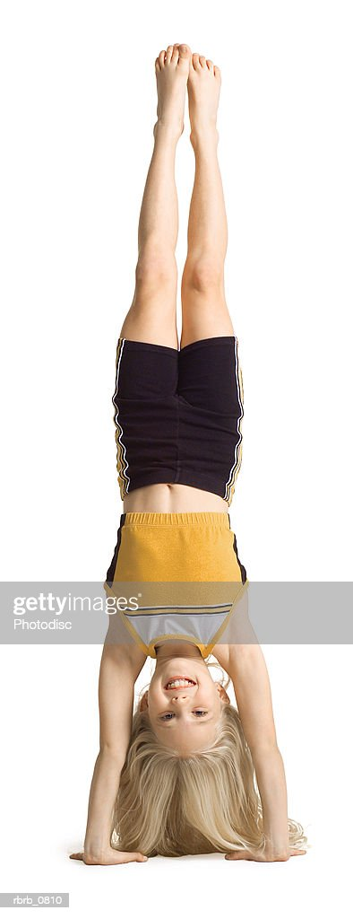 silhouette of a caucasian blonde female child dancer in a black and yellow outfit as she stands on her head : Stockfoto