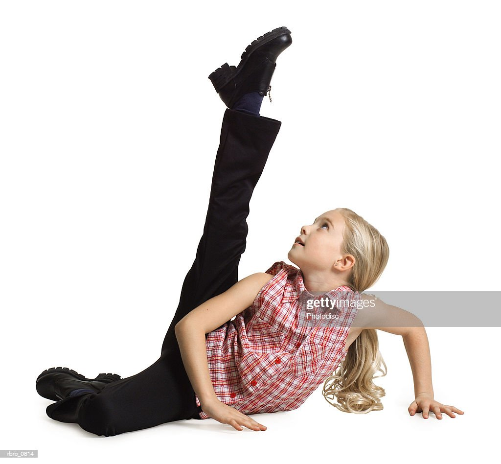 silhouette of a caucasian blonde female child  in black pants and a plaid shirt as she kicks up into the air : Stockfoto