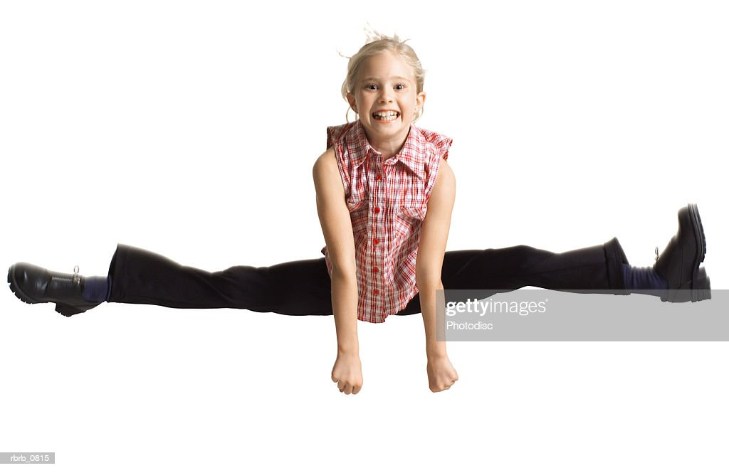 silhouette of a caucasian blonde female child  in black pants and a plaid shirt as she jumps up and does the splits : Stock Photo