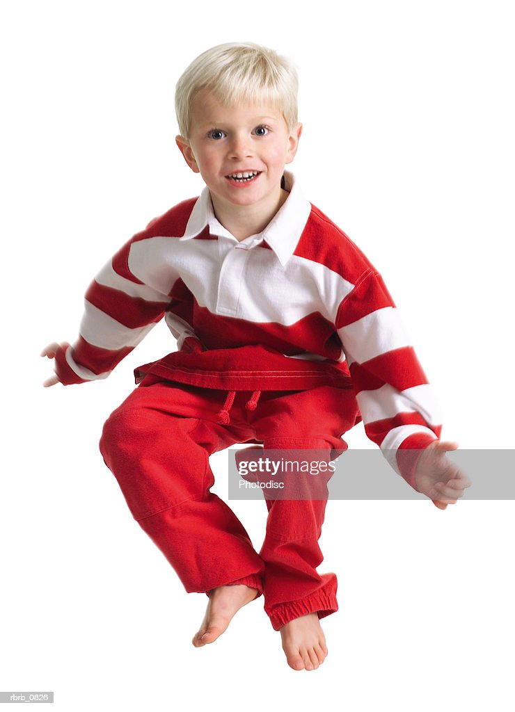 silhouette of a caucasian blonde male child in red pants and a stripped shirt as he hops up in the air : Stockfoto