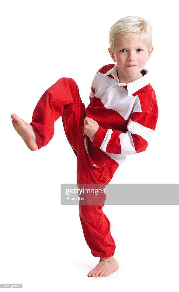 silhouette of a caucasian blonde male child in red pants and a stripped shirt as he kicks to the side : Stockfoto