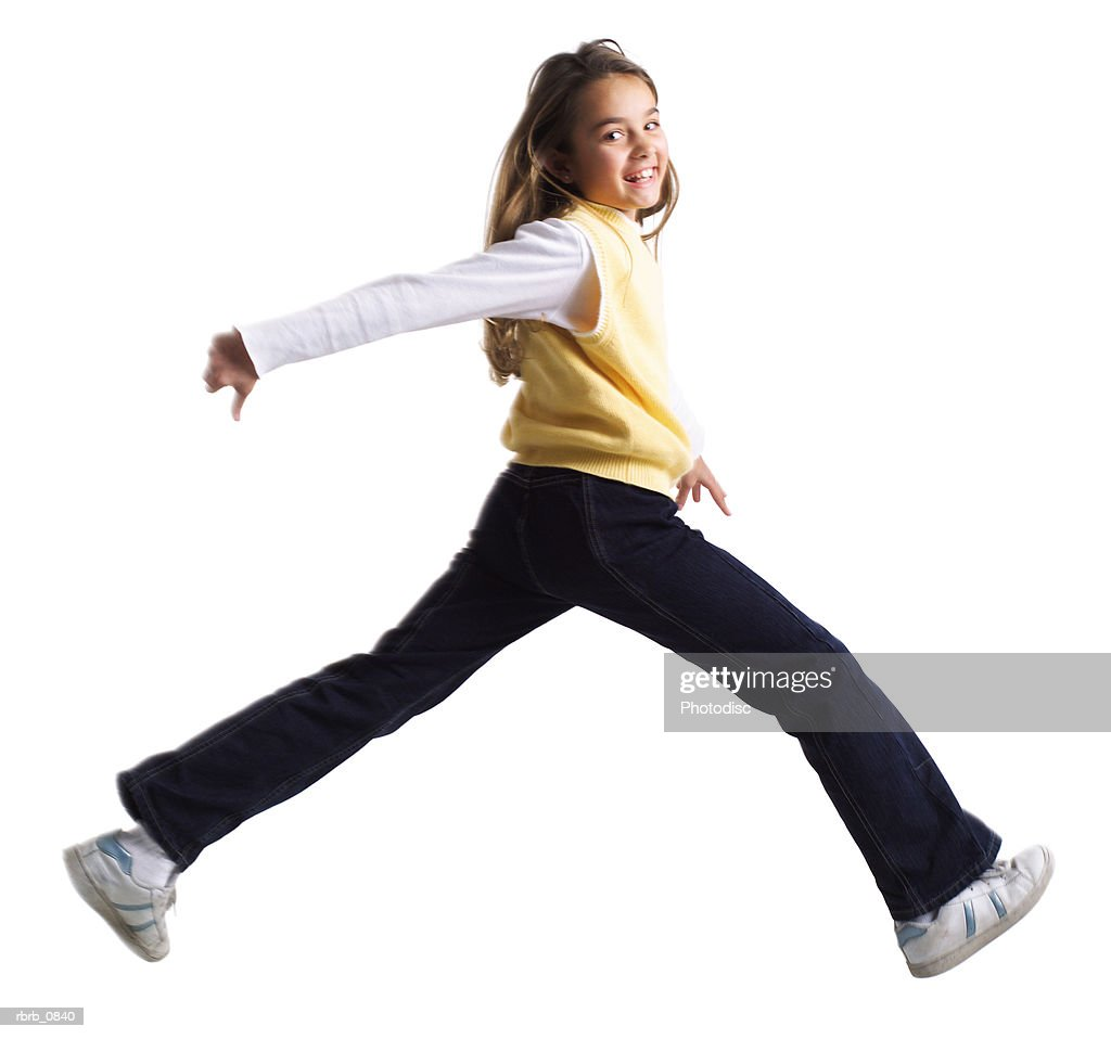 silhouette of a caucasian female child in a yellow sweater as she runs and jumps : Stockfoto
