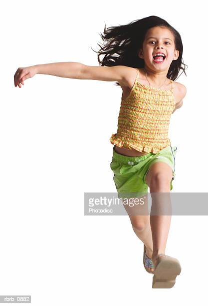 silhouette of a caucasian female child in green shorts and a yellow shirt as she runs and jumps