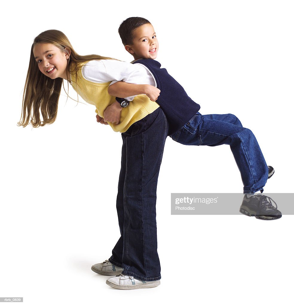 silhouette of a caucasian female child lifts up her little brother on her back as they both smile : Stockfoto